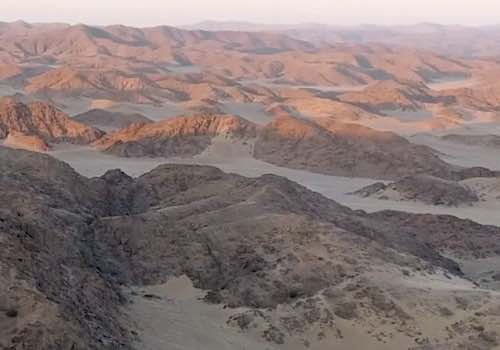 The red rocks of the desert mountains of Namibia gleam under the rising sun.