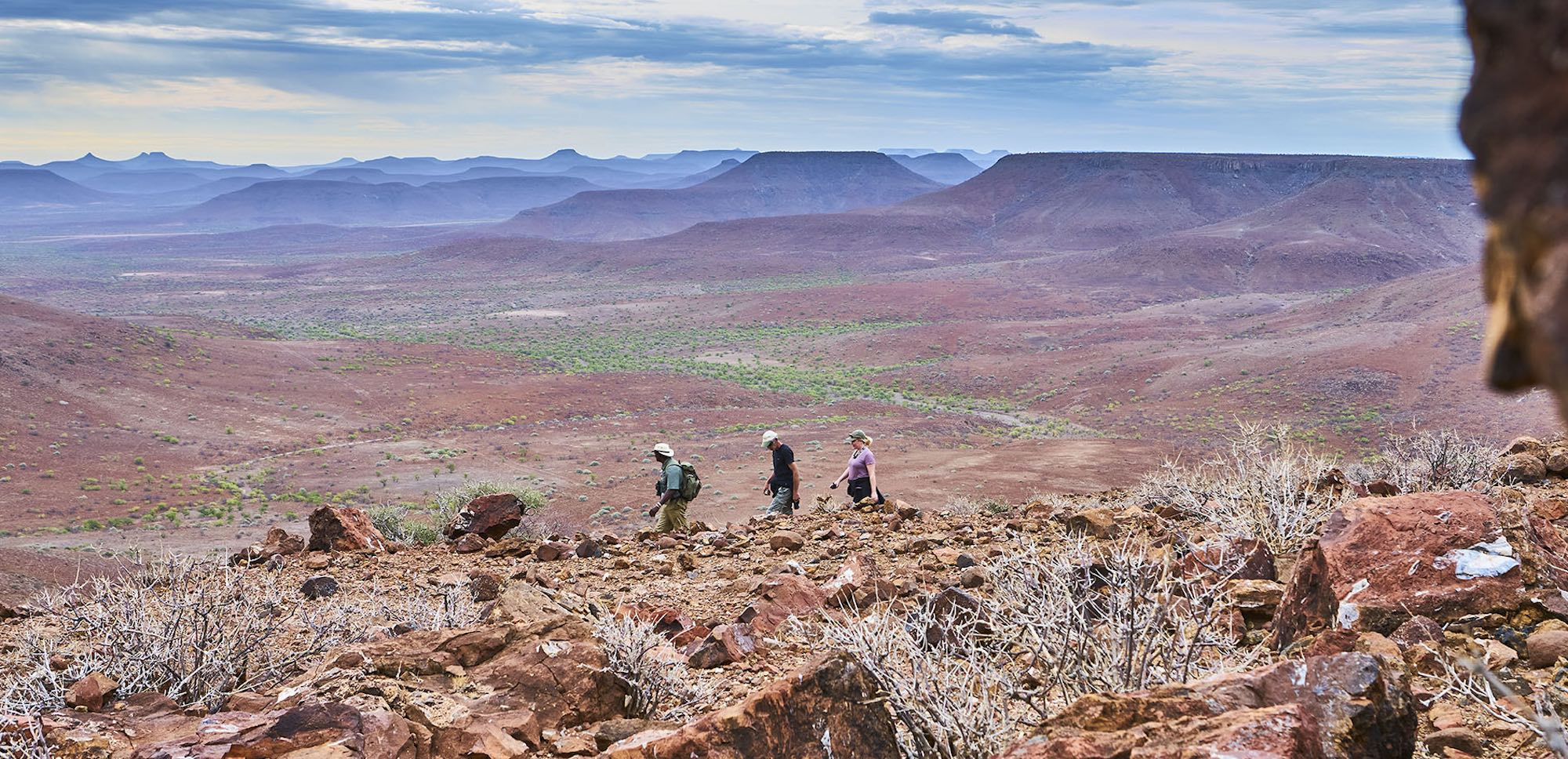 A guide leads three tourists along a rocky trail overlooking the stunning scenery of northern Namibia.