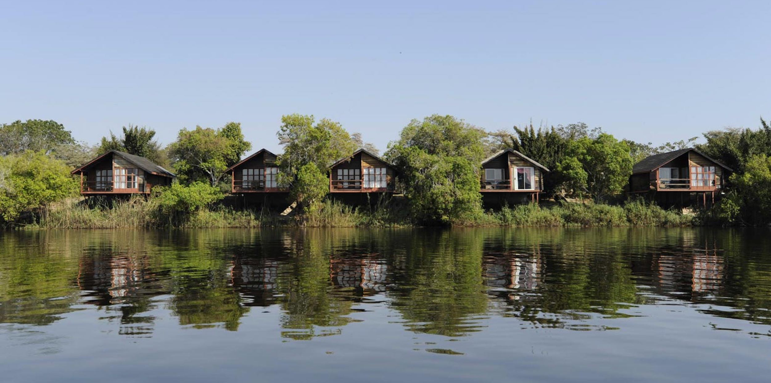 Luxury chalets peer out from amongst lush greenery overlooking the river.