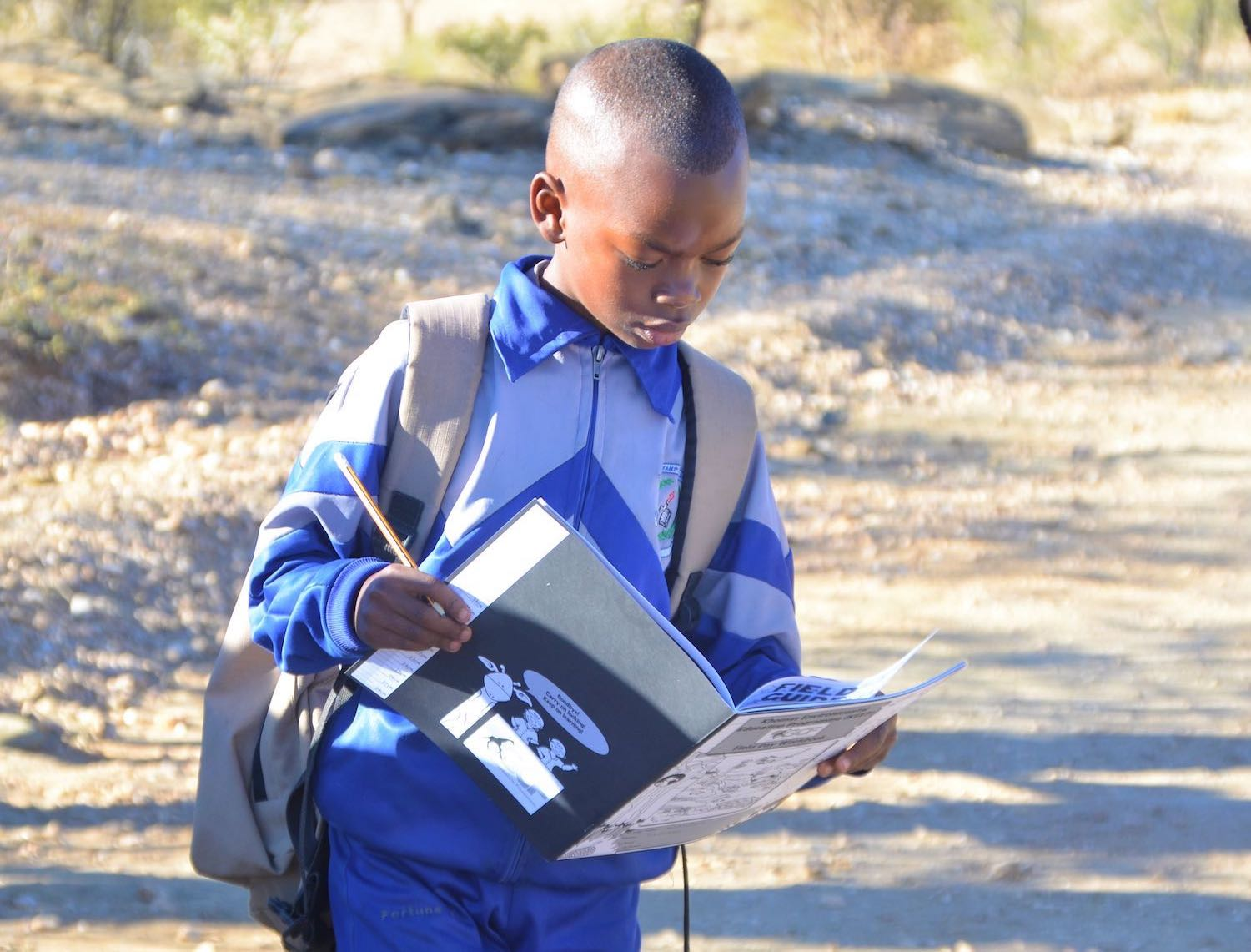 A young learner looks intently at his KEEP notebook.