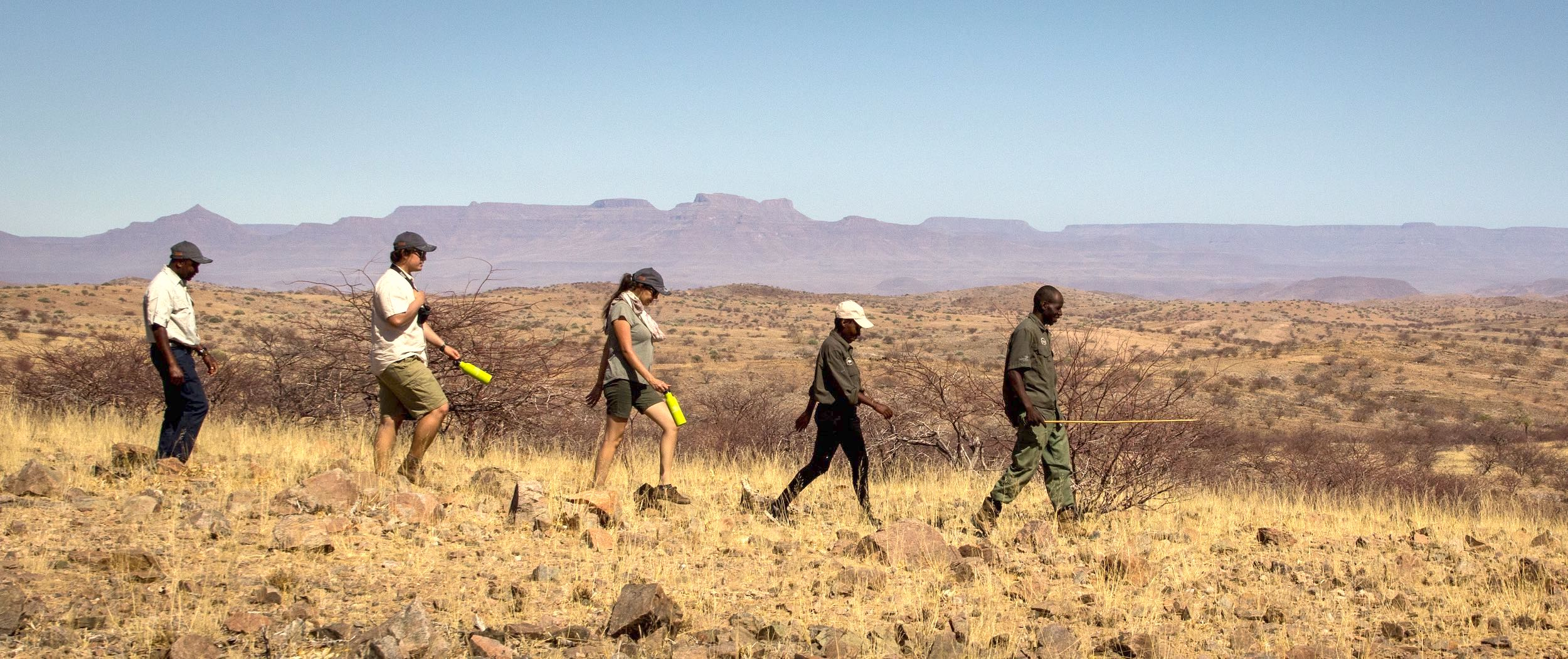 A guide leads a group of tourists on a trek across the stunning scenary of north-western Namibia.