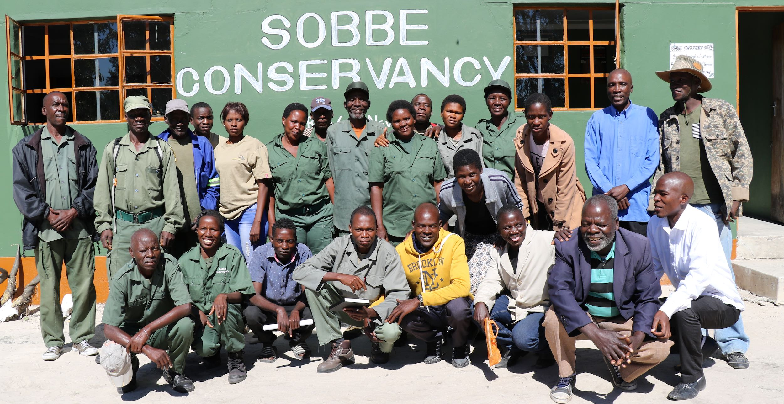 A group of Namibian men and women pose outside a green building.