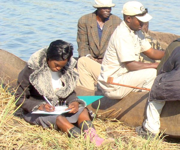 A community fisheries inspector records details of the catch as a group of fishmen unload their boat.