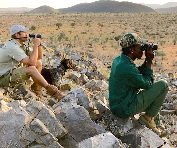 A hunter, his guide, and a dog, stare into the distance looking for wildlife