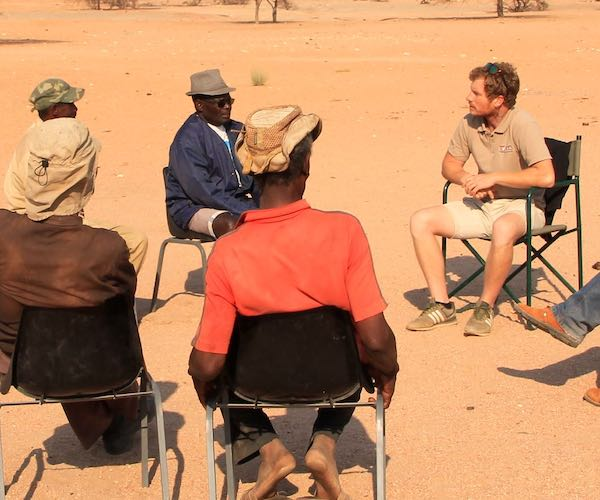A group of people sitting on a circle of chairs in the desert - a meeting with a view!