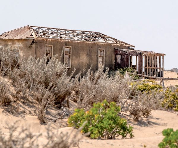 A decaying house being taken over by the desert